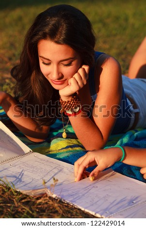 Beautiful multicultural young college woman studying outdoors on campus. - stock photo