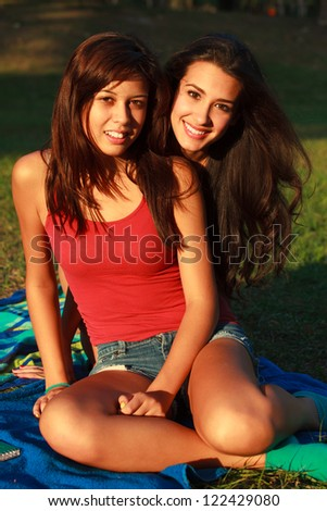Beautiful multicultural young college women enjoying outdoor campus life.
