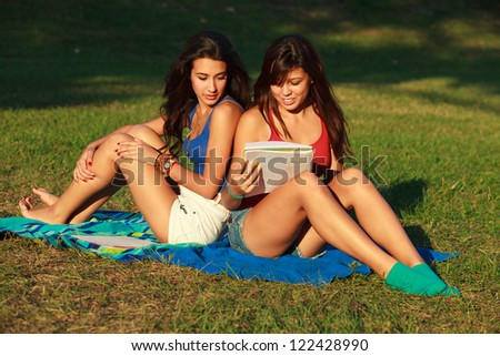 Beautiful multicultural young college women studying outdoors on campus. - stock photo