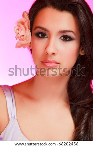 Beautiful multicultural young woman in a beauty studio portrait pose with a purple background.