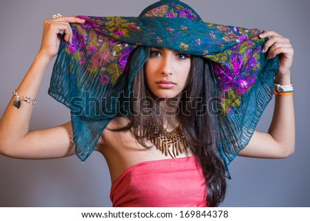 Beautiful multicultural young woman studio portrait wearing a purple veil.