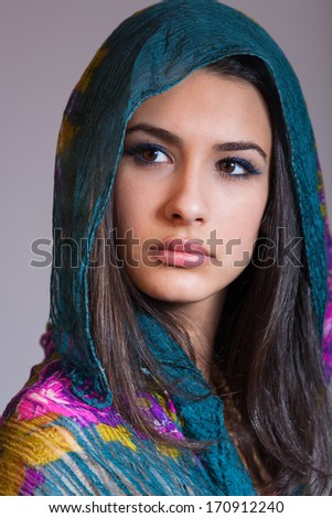 Beautiful multicultural young woman studio portrait wearing a purple veil. - stock photo