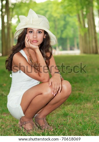 Beautiful multiracial young woman in a fashion pose in the Gardens of the Palace of Versailles in Paris, France. - stock photo