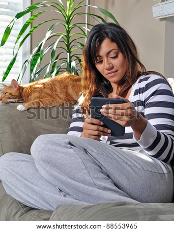 Beautiful multiracial young woman sits on a couch, smiling, in a casual sweater and sweats using an e-reader while an orange cat sleeps behind her - stock photo