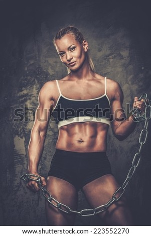 Beautiful muscular bodybuilder woman holding chains - stock photo