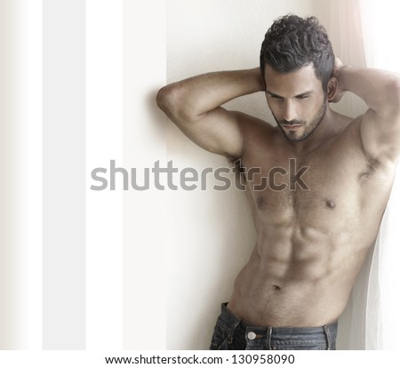 Beautiful muscular male model with nice abs in jeans near window with copy space - stock photo