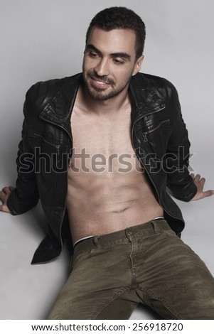 Beautiful muscular male model with nice abs in leather jacket - stock photo