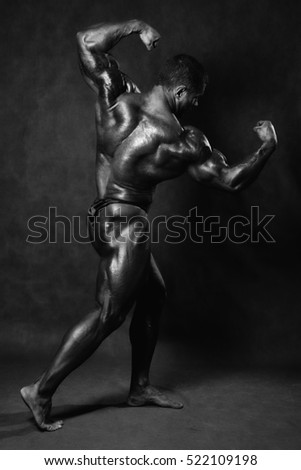 Beautiful muscular man's back in the studio on a black background.