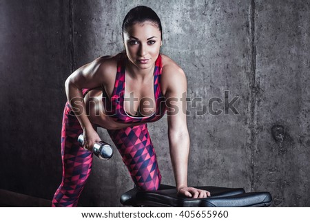 Beautiful muscular woman doing exercise with dumbbells on a gray background.Concrete wall in the background