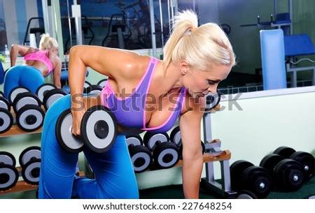 Beautiful muscular woman exercising in a gym - stock photo