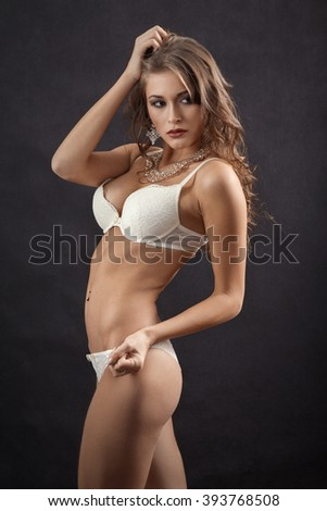 beautiful muscular woman in white lingerie on black background, toned image