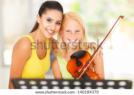 beautiful music teacher with young violin student - stock photo
