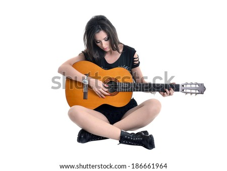 Beautiful music woman holding a guitar isolated on white
