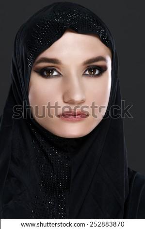 Beautiful muslim arabic woman on grey background - studio shot - stock photo