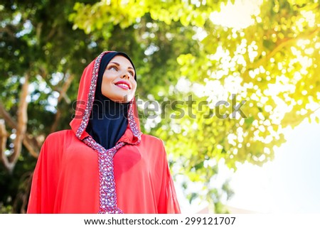 beautiful muslim caucasian woman wearing red dress and hijab in the park