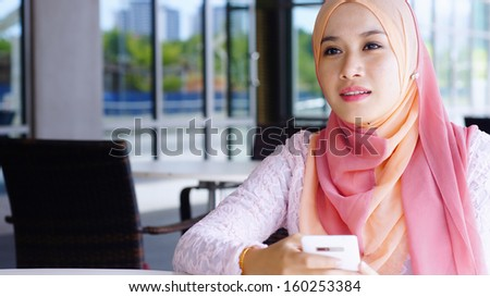 Beautiful Muslim girl holding mobile phone at the cafe