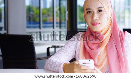 Beautiful Muslim girl holding mobile phone at the cafe - stock photo