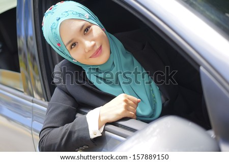 Beautiful Muslim girl in a car  - stock photo