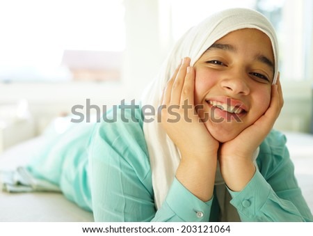 Beautiful Muslim girl lying down with hijab and smiling - stock photo