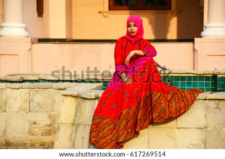 Beautiful muslim girl sitting in front of the building post for fashion