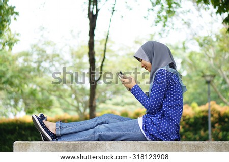 Beautiful muslim girl with her smartphone in a park - stock photo