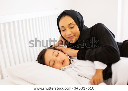 beautiful muslim mother watching her son sleeping in bed - stock photo