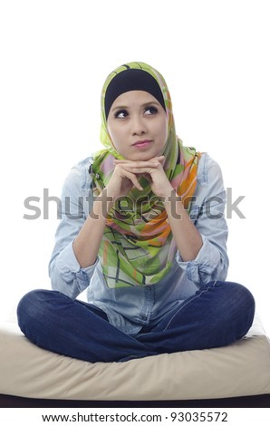 beautiful muslim woman sitting with cross-legged on a couch and thinking for someone