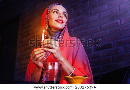 Beautiful muslim woman waiting for an evening time to take Iftar - evening meals of Ramadan month - stock photo