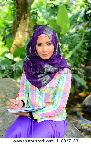 Beautiful muslim woman wearing scarf with a book study at a garden