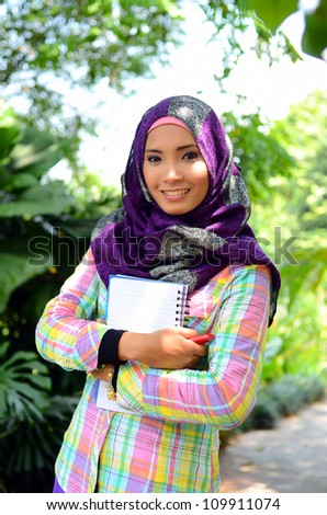 Beautiful muslim woman wearing scarf with notebook