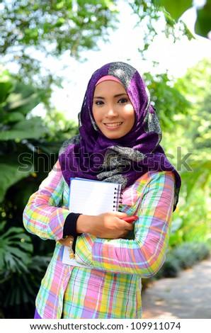 Beautiful muslim woman wearing scarf with notebook - stock photo