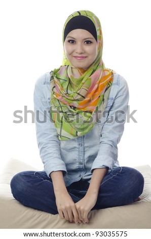 beautiful muslim woman with stylish head scarf smiling and sitting cross-legged on a couch - stock photo
