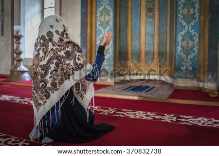 Beautiful Muslim young woman praying in masjid - stock photo