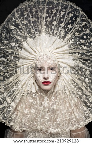 Beautiful mysterious woman in regal lace collar - stock photo