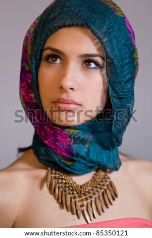 Beautiful mysterious young multicultural woman wearing a purple shawl.