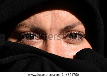 beautiful mysterious young woman wearing black scarf close up - stock photo
