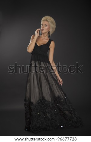 Beautiful mystic lady in black dress in dark studio - stock photo