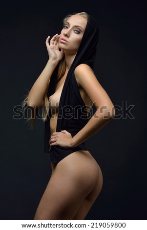 Beautiful naked blonde woman in a black blouse posing in a dark Studio - stock photo