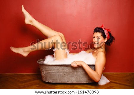 beautiful naked brunette bathes in a metal tub, she is covered with bath foam, glamour and pin up photography - stock photo