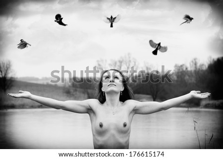 Beautiful naked brunette with the birds posing near the pond, in a nature, winter, nude photography, black and white photo - stock photo