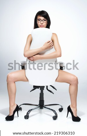beautiful naked dark-haired woman sitting on white chair. nude young girl sitting and looking at camera - stock photo