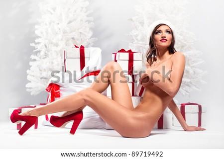 Beautiful naked female posing over winter background - stock photo