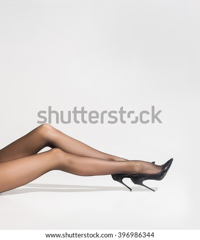 Beautiful naked legs in pantyhose over white background - stock photo