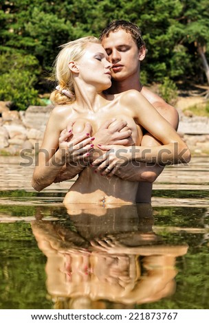 Beautiful naked man and woman kissing in the water outdoors.