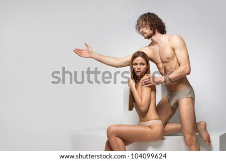 beautiful naked man and woman poziruyutna white cubes - stock photo