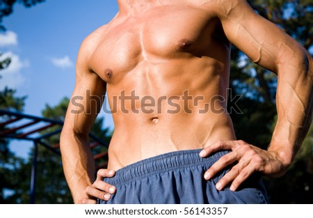 beautiful naked muscular body of a young man on outdoors. Unrecognizable - stock photo
