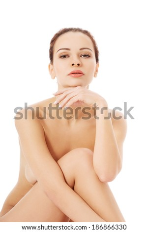 Beautiful naked woman sitting. Isolated on white.