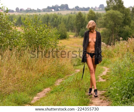 Beautiful naked woman walking at the meadow - stock photo