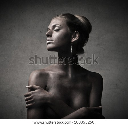 Beautiful naked woman with painted skin wearing earrings - stock photo