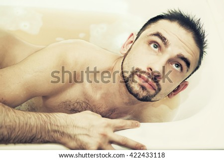 Beautiful naked young man lying in a bathtub